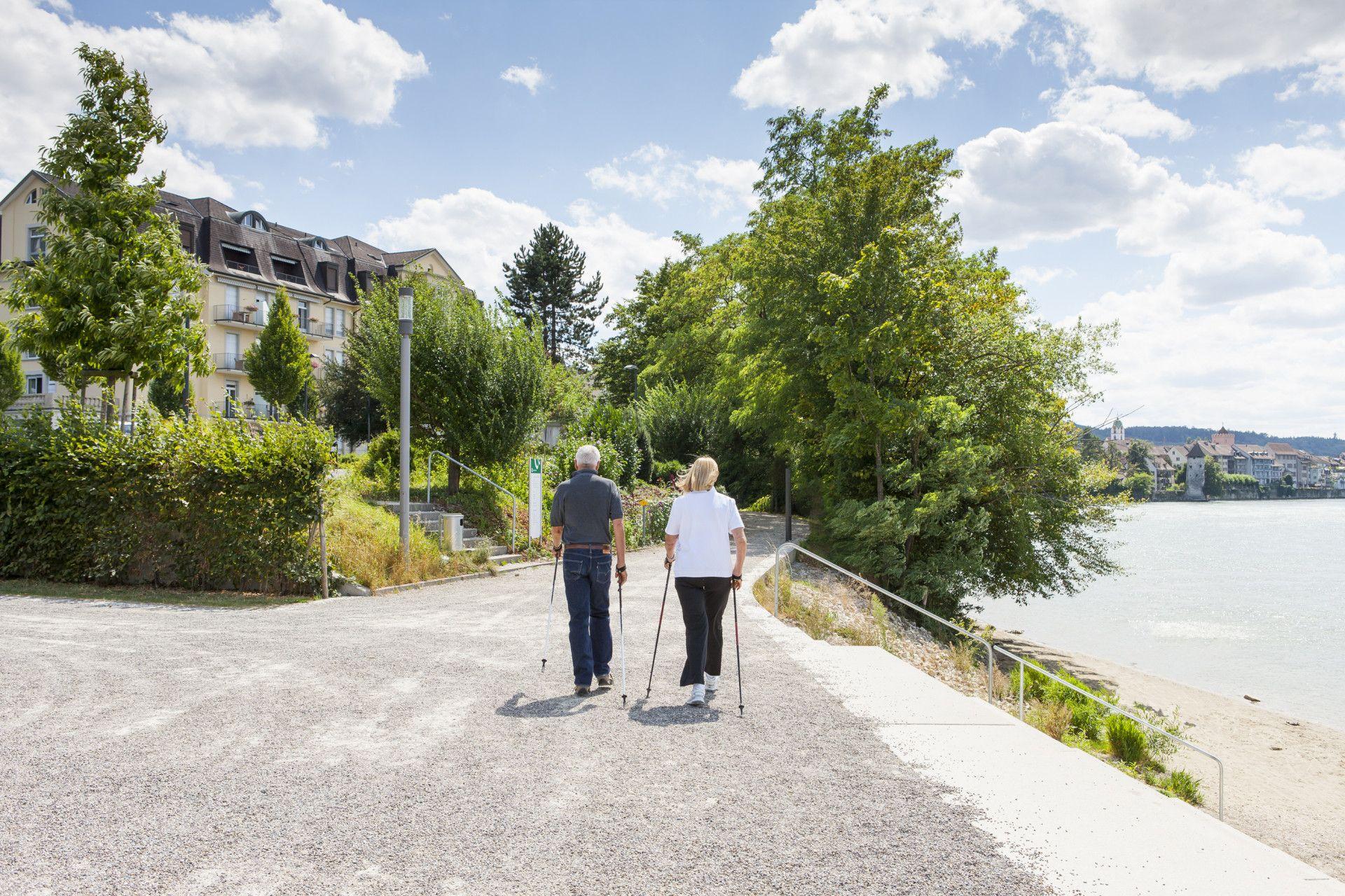 Mann und Frau laufen mit Nordic-Walking-Stöcken am Rheinufer vor Park-Hotel