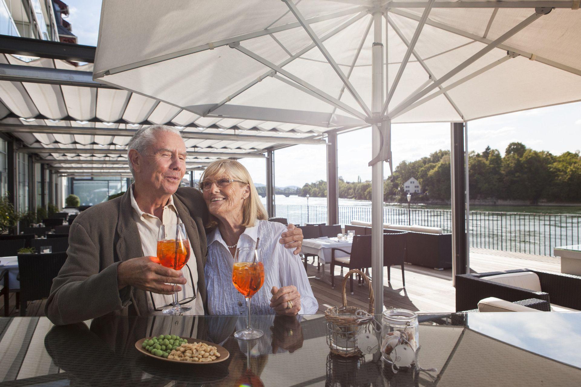 Ältere Gäste stossen auf Rheinterrasse mit Apérol an