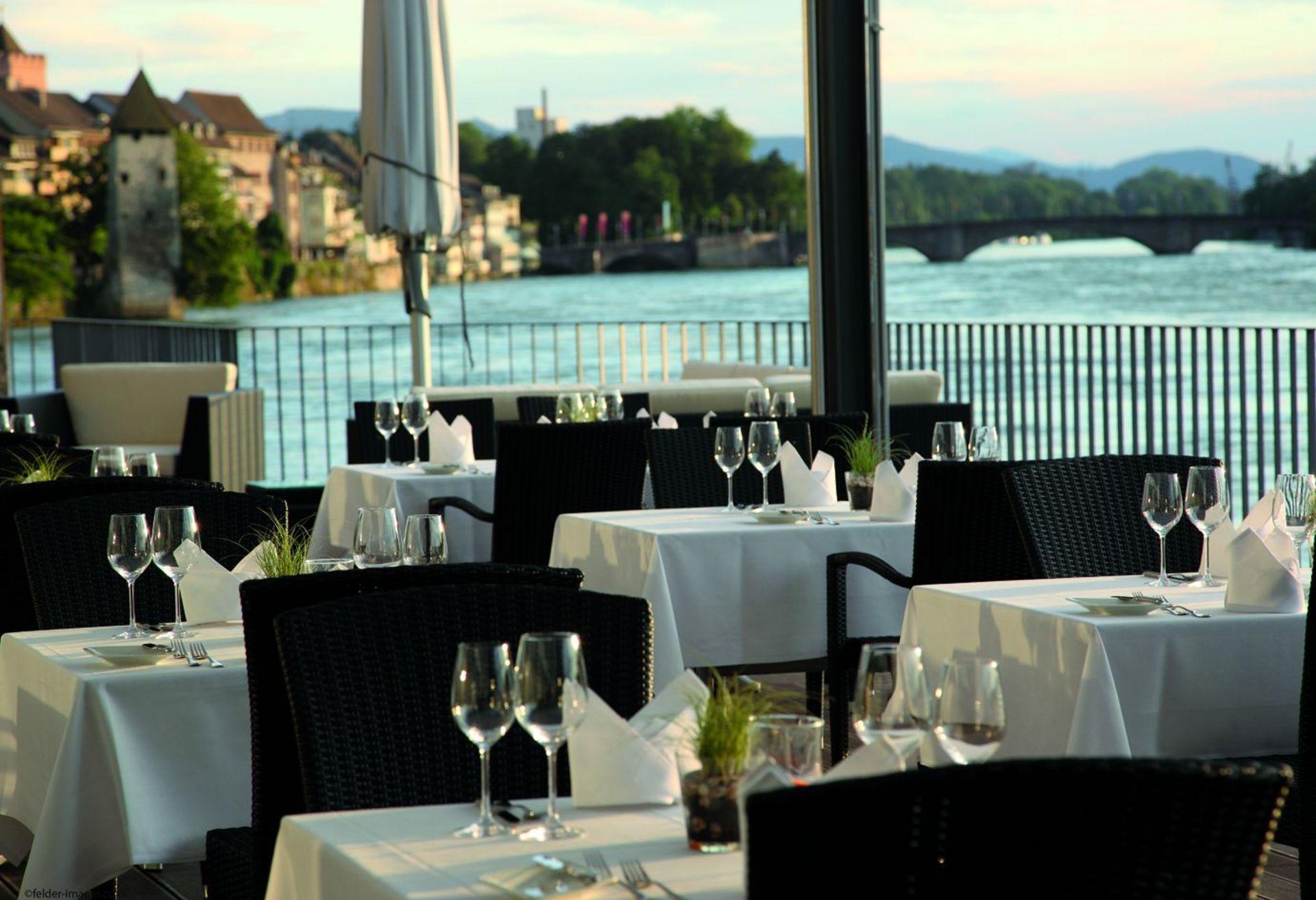 Eingedeckte Tische auf Rheinterrasse ohne Gäste