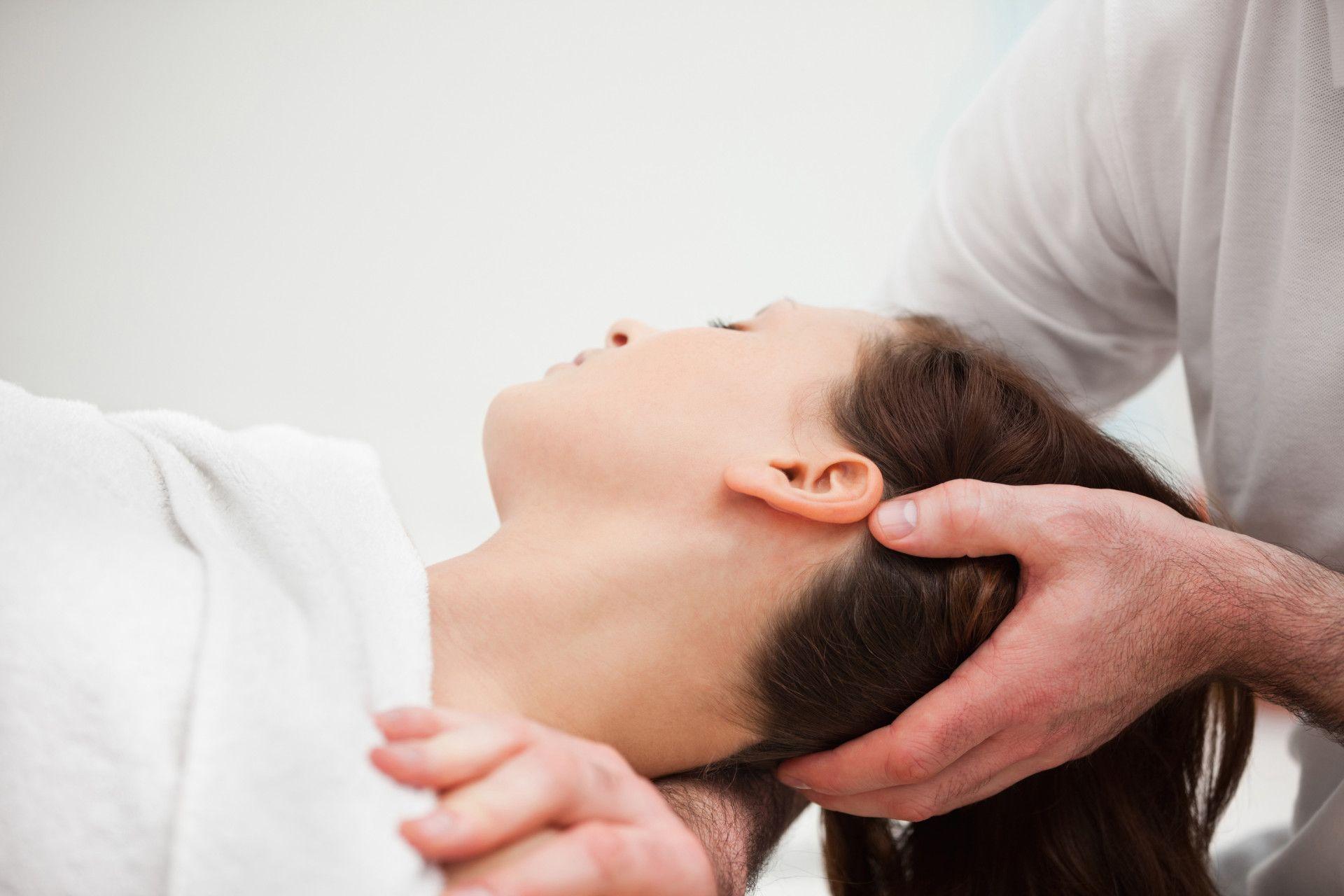 Therapeut macht Übung am Halswirbel einer Patientin