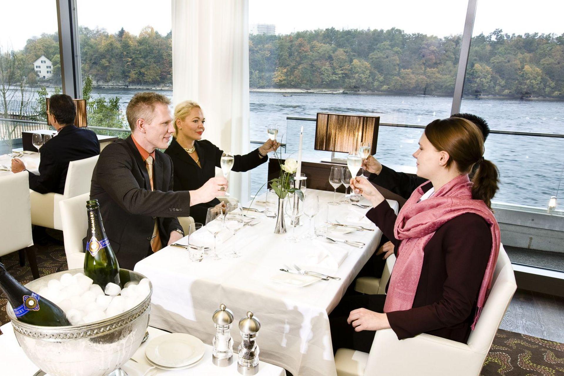 Vier Gäste am Tisch stossen an im Restaurant Bellerive