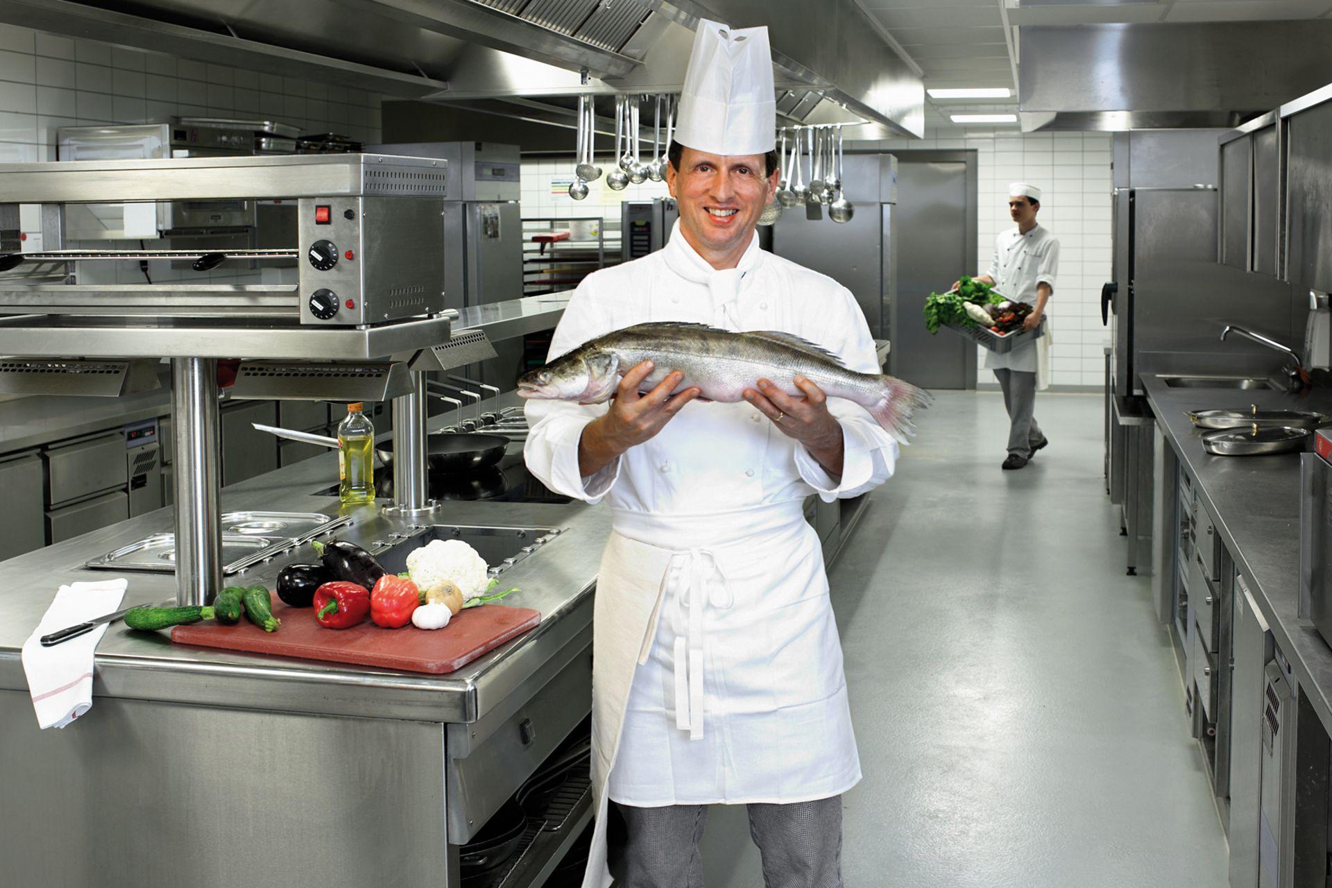 Chefkoch in der Hotel-Küche hält einen Fisch in der Hand