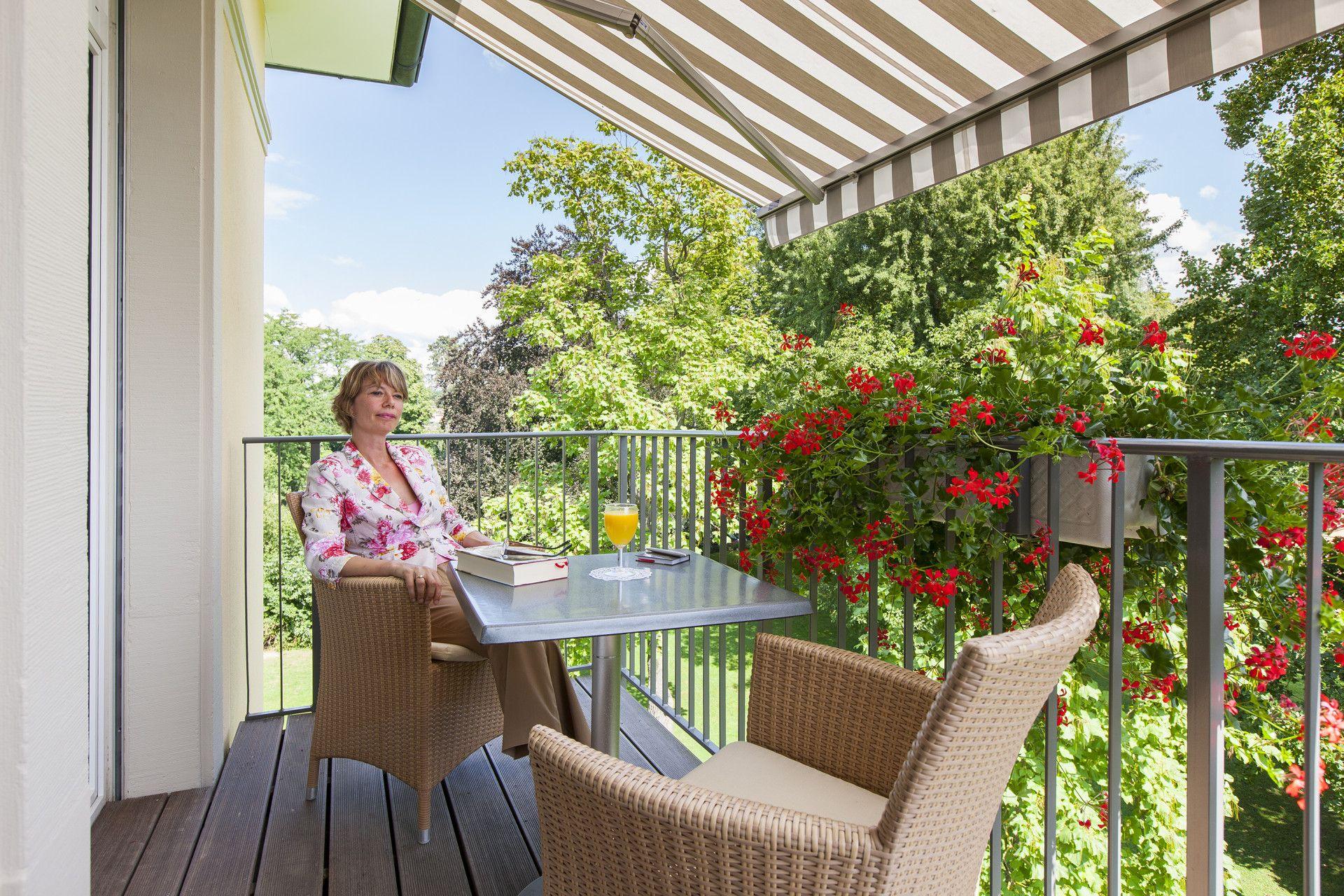 Frau sitzt auf Balkon und geniesst sommerlichen Park-Blick