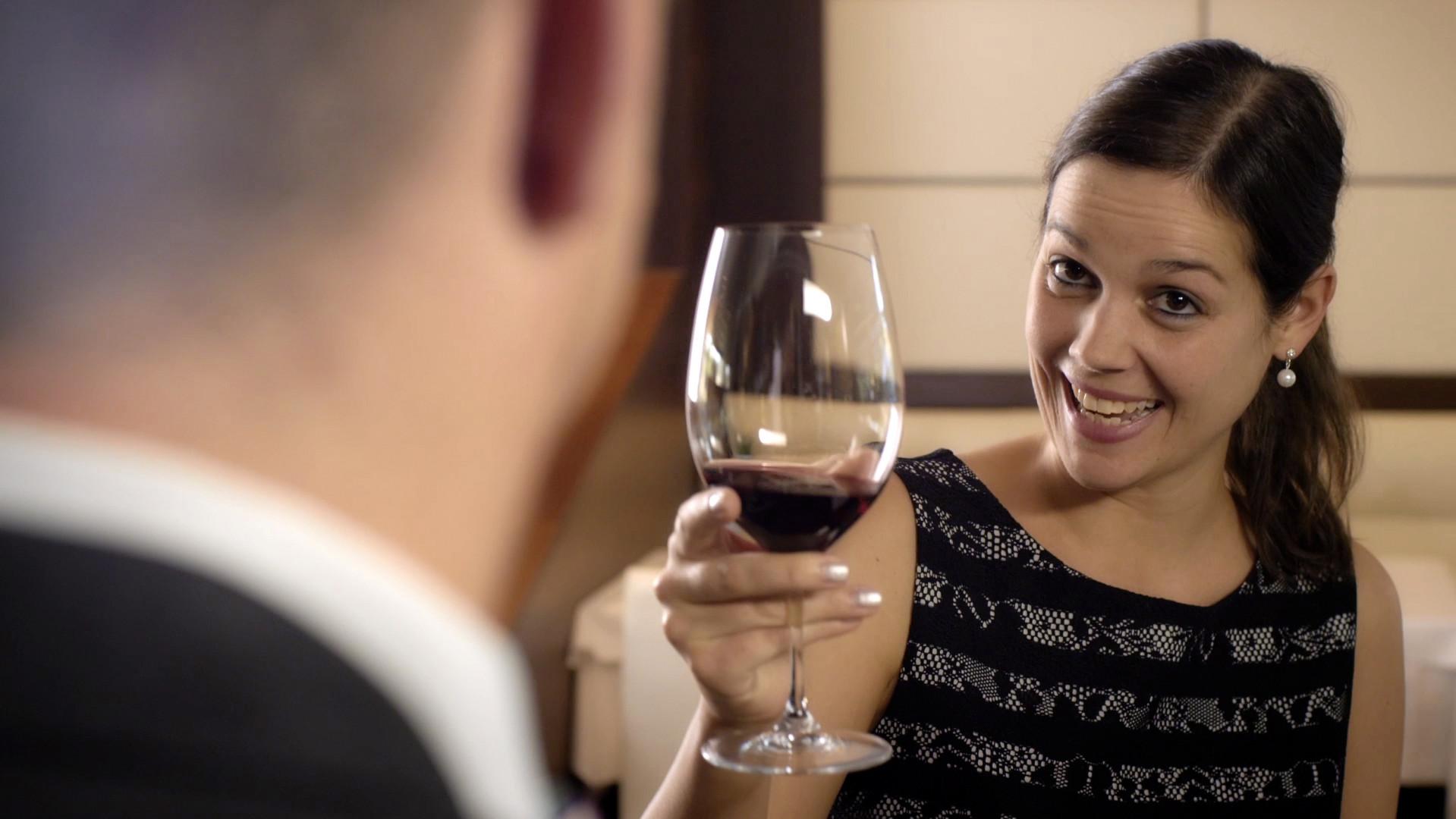 Mann und Frau stossen mit einem Glas Wein an