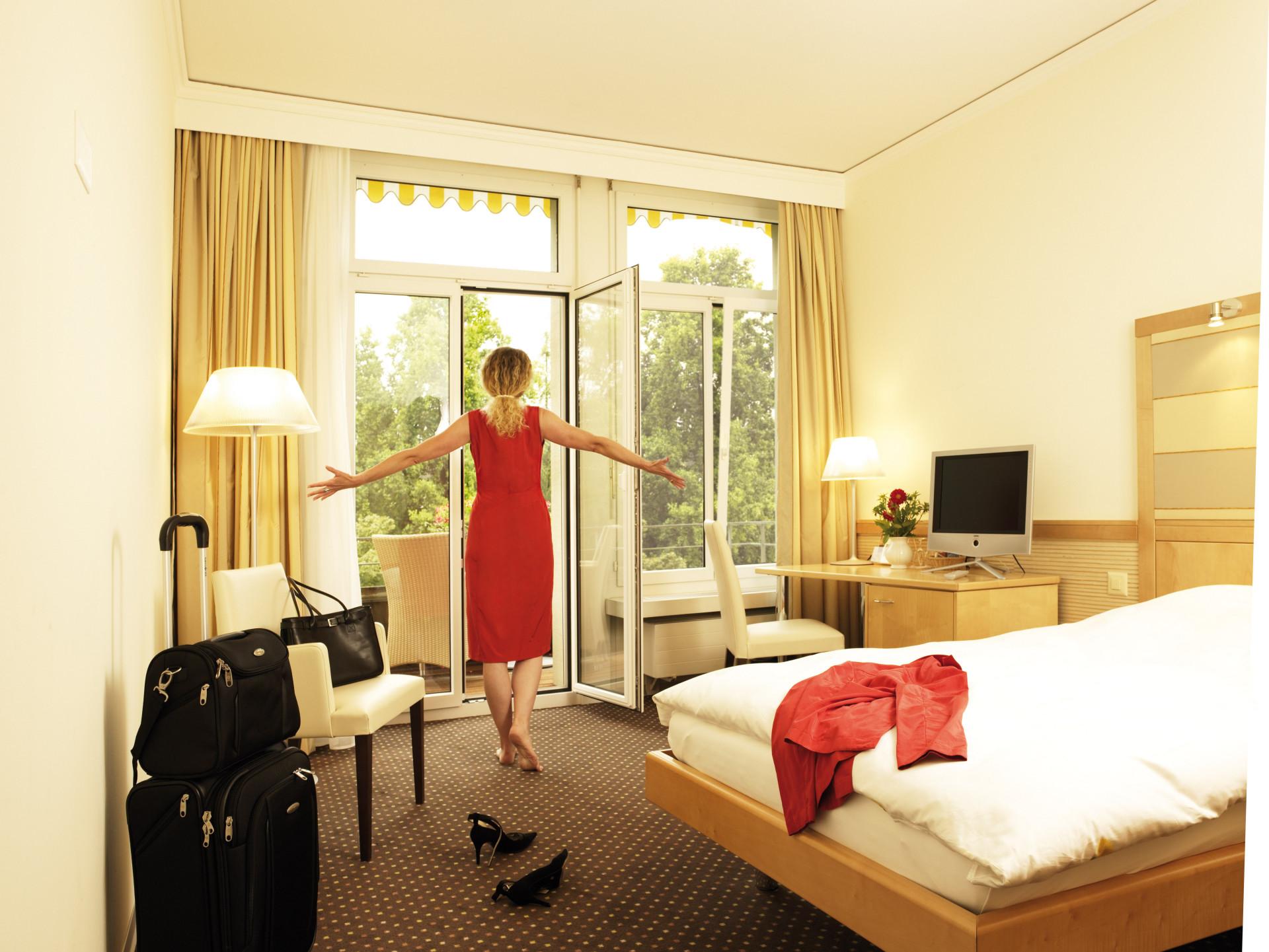 Frau öffnet Balkontür im Doppelzimmer im Park-Hotel am Rhein