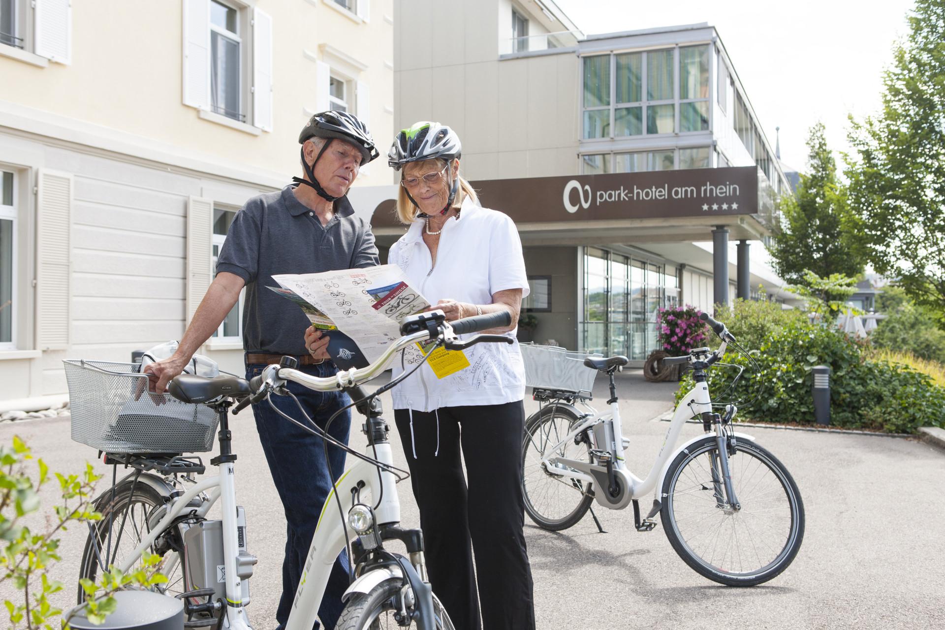 Mann und Frau mit E-Bikes und Velokarte vor Park-Hotel am Rhein