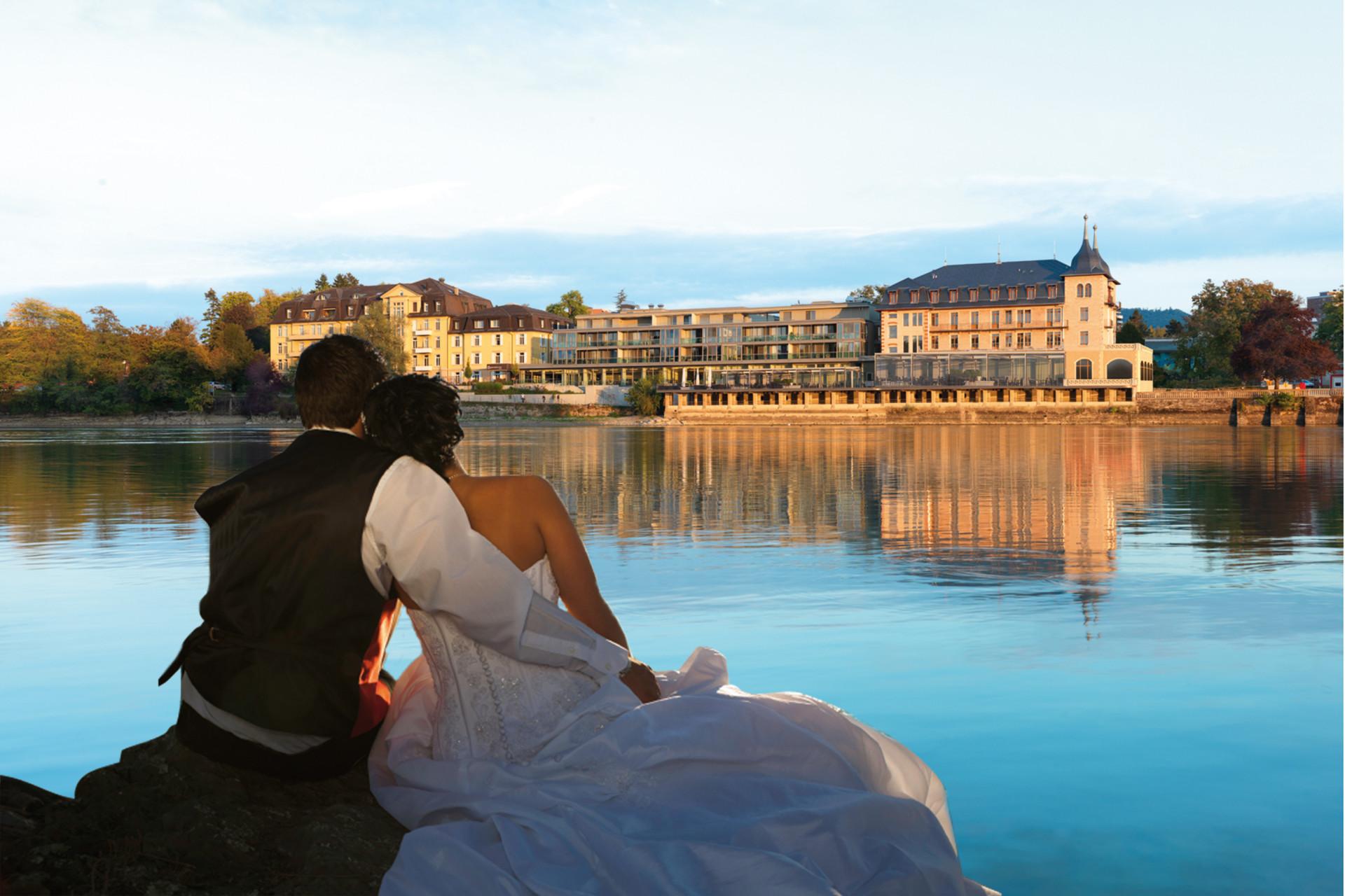 Brautleute sitzen am anderen Ufer des Rheins und schauen auf Park-Hotel