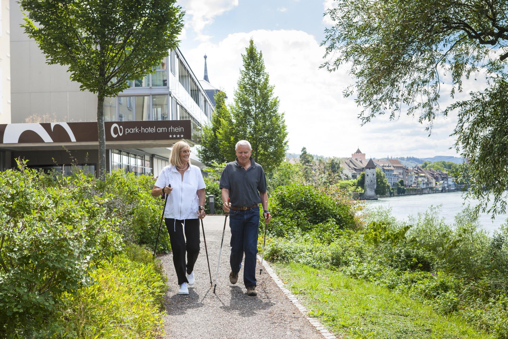 Mann und Frau laufen mit Nordic-Walking-Stöcken vor Hoteleingang los