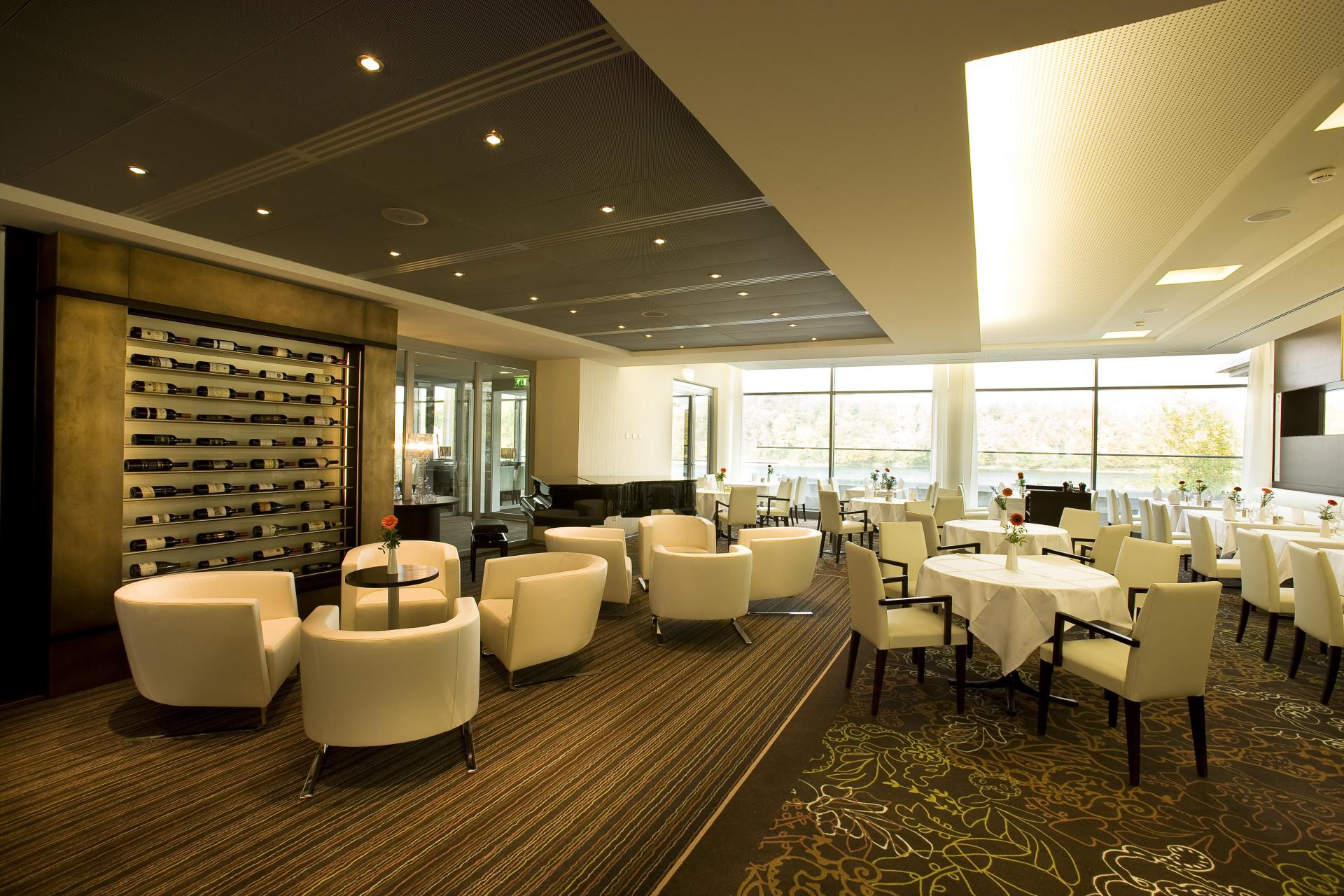 Lounge im Park-Café ohne Gäste mit Weinregal im Hintergrund