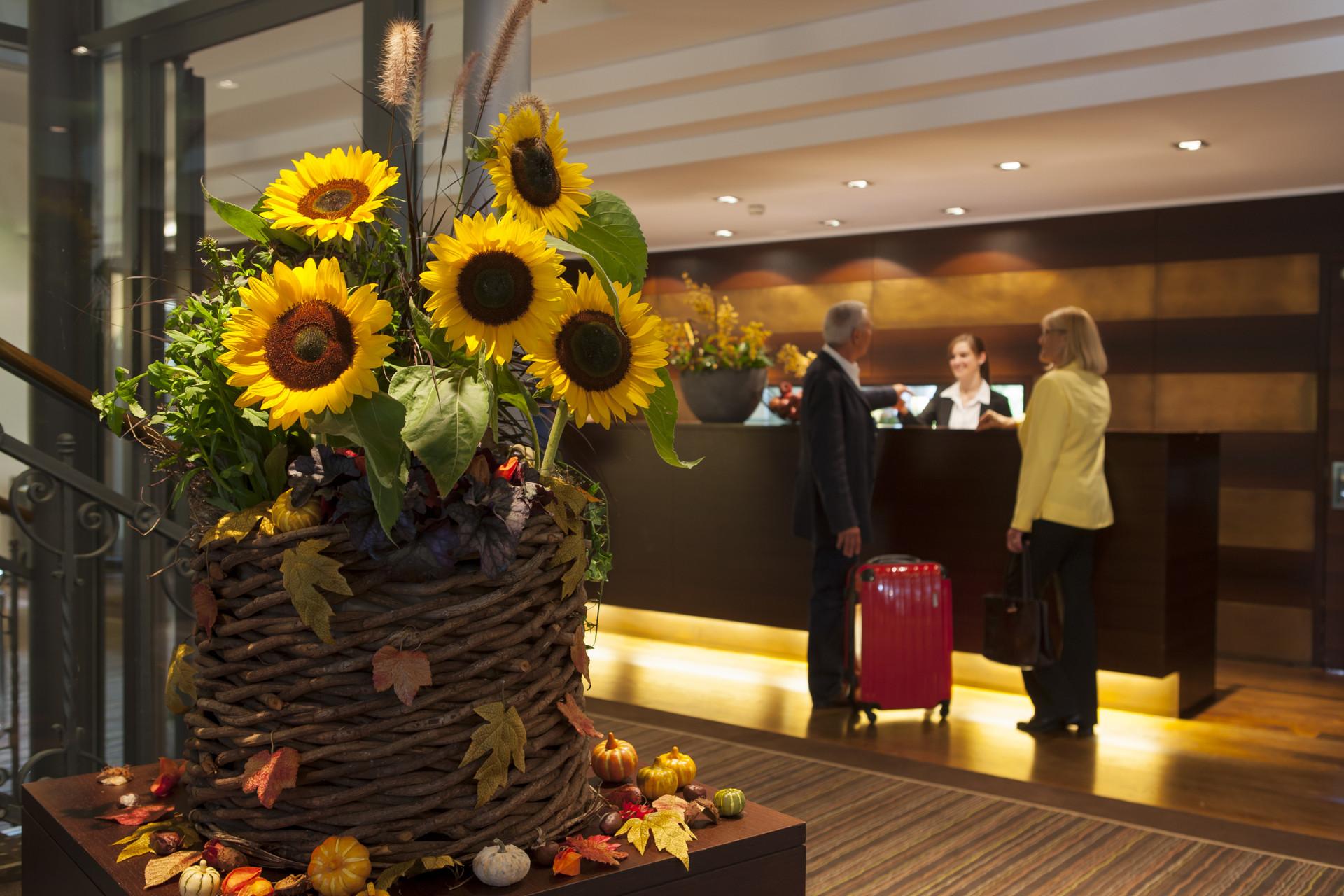 Gäste an Réception mit Sonnenblumen im Vordergrund