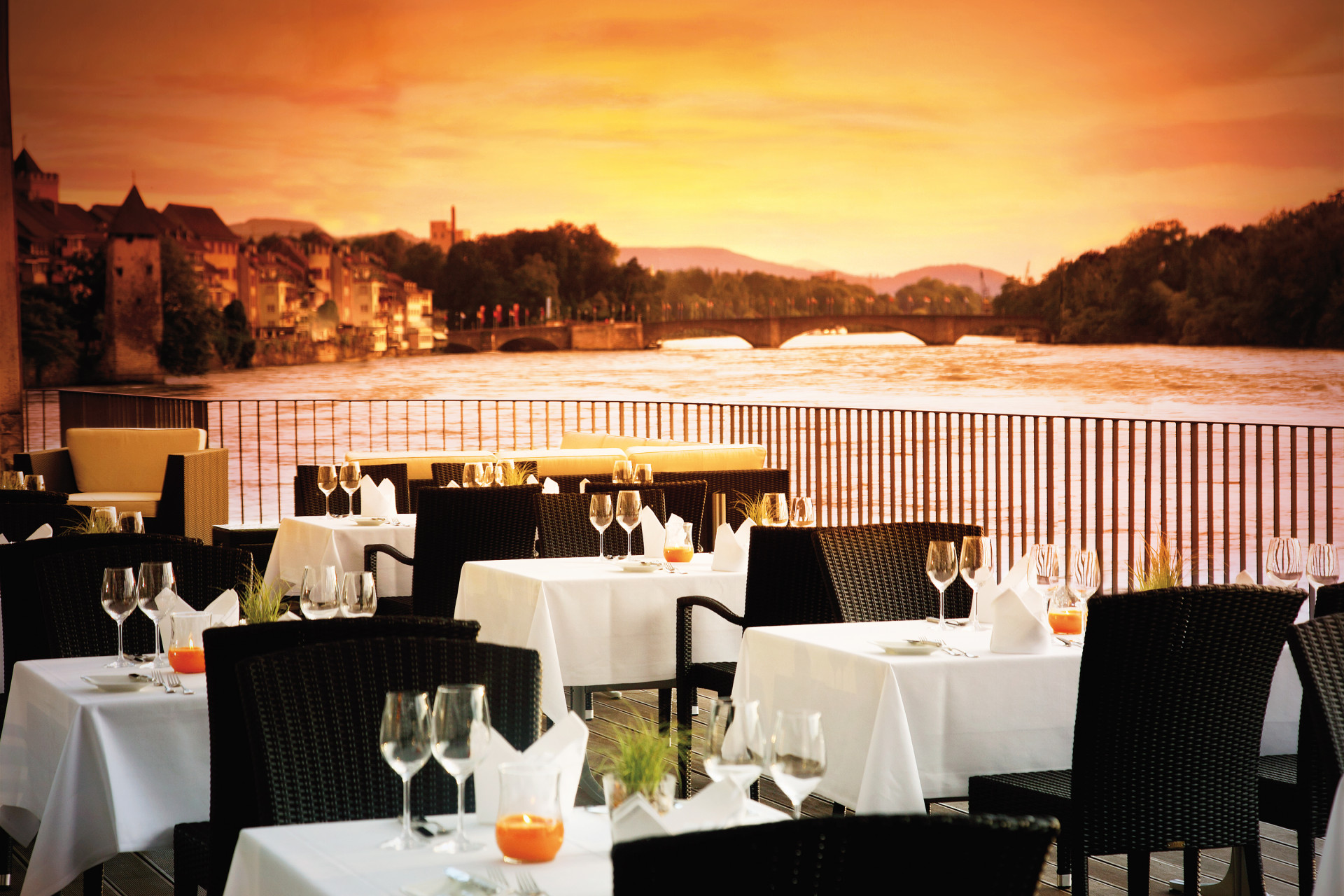 Abendstimmung mit orangem Himmel auf eingedeckter Rheinterrasse ohne Gäste