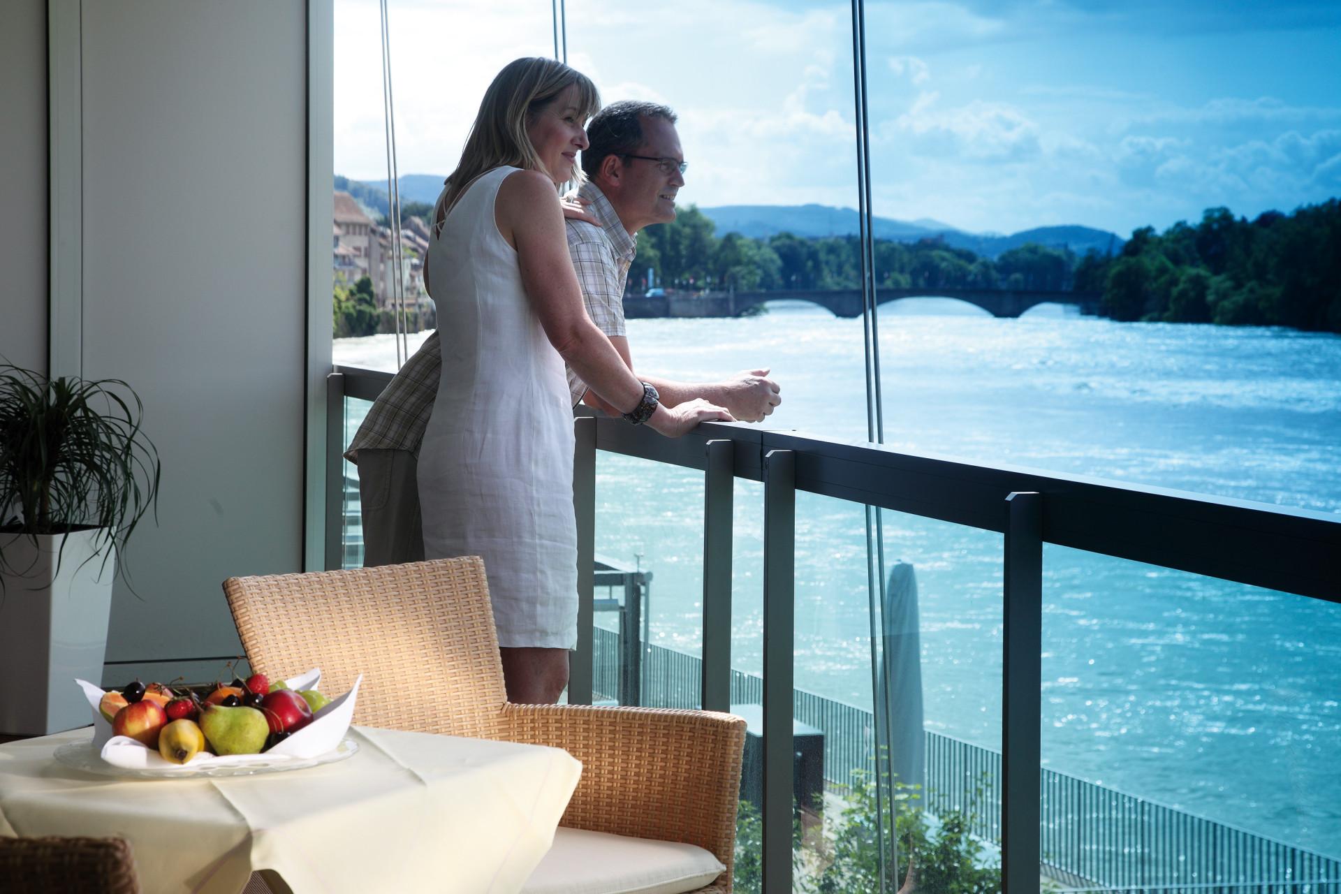 Paar steht auf Balkon und geniesst Blick auf den Rhein